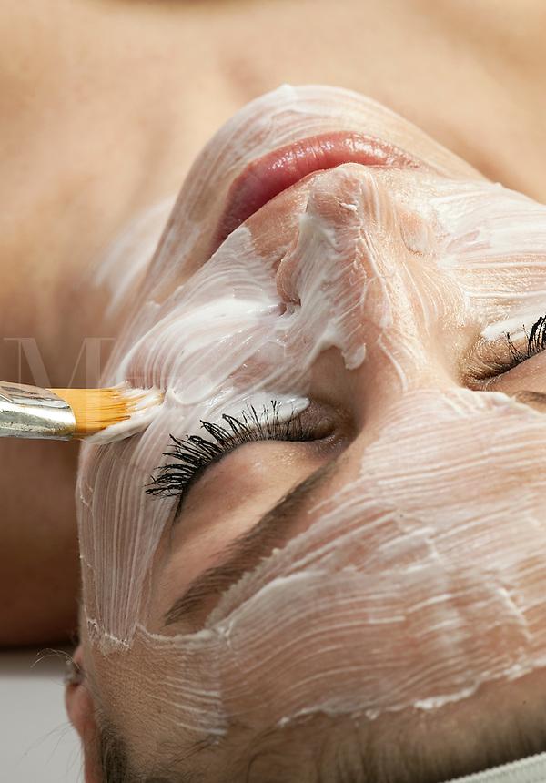 Woman getting a facial treatment at a spa.