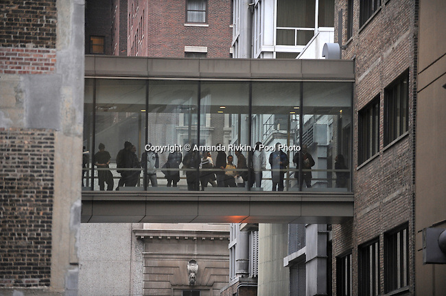 Onlookers gather as President Elect Barack Obama's motorcade waits outside the Johnson Publishing Company, publisher of Ebony and Jet, in Chicago, Illinois on Nov. 13, 2008.  Obama is working mostly in the Chicago area as he prepares for his transition to become the 44th U.S. President.