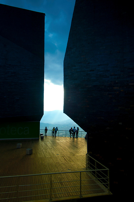 Visitors enjoy the view from the Biblioteca Espana, a library and park that has transformed the once dangerous steep hillside barrio of Santo Domingo in Medellin, Colombia.  The library consists of three giant black geometric buildings that look like rocks rising out of the hillside.