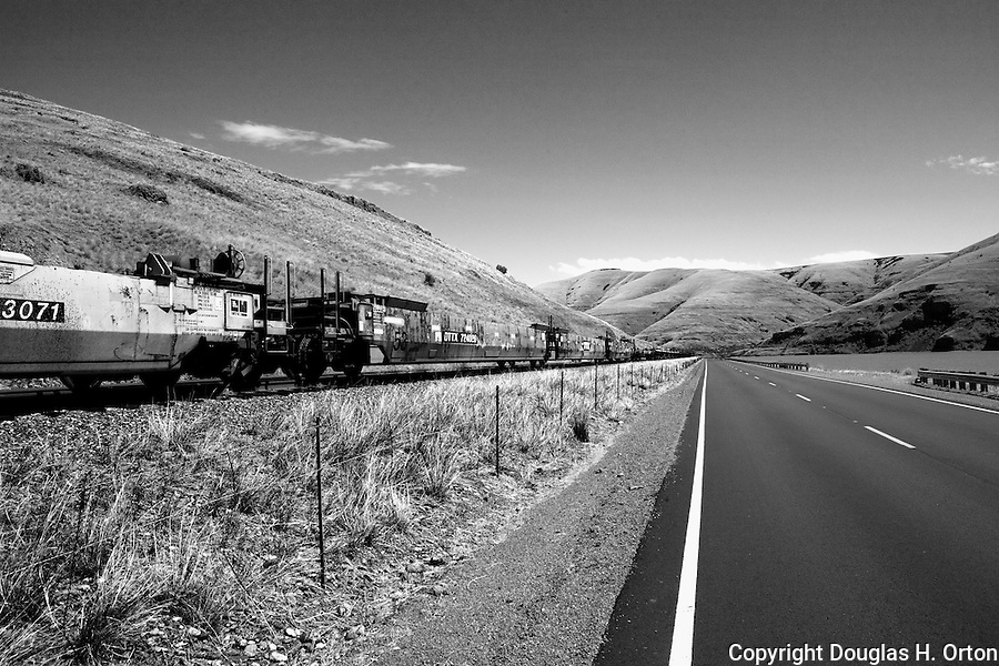 Railroad cars and highway along the Snake River canyon near Wawawai, in Washington State Palouse country.  Demonstrates Parallax effect.
