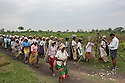 India – West Bengal: Pluckers at Mogulkata Tea Estate, in the Dooars region, waiting in line at a weighting point operated by a manager. The tea estates' managerial staff still dresses in shirts and shorts, in homage to the old customs set by the British during colonialism.