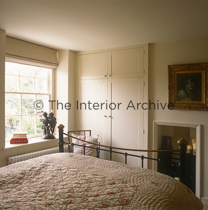 A country bedroom decorated in neutral tones and an original cast-iron fireplace set in a recess. The room has a brass bedstead with a floral pattern quite cover.