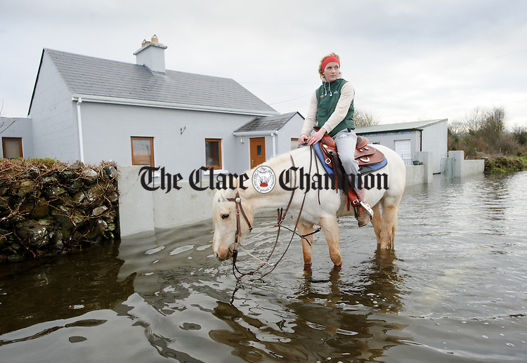 Shannon Kent rides her horse on the road outside her grandmother Nancy Walsh's flooded home at Caherbroder Gort adjacent to the M18 motorway.  Photograph by John Kelly.