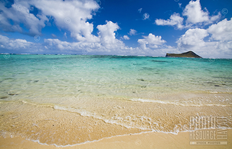 Beach in Waimanalo with clear blue water over coral and sand, with a view of Rabbit Island