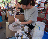 The Ice Berg Ice Cream Roll kiosk prepares frozen rolls of ice cream with toppings in Vendy Plaza at La Marqueta in the East harlem neighborhood of New York on Sunday, June 19, 2016. The plaza area under the MetroNorth tracks, La Marqueta Retoña, hosts a weekly vendors market drawing on food entrepreneurs from the streets around the city. (© Richard B. Levine)