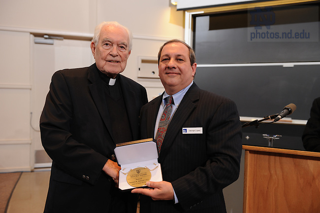 Kroc Institute professor George Lopez and Rev. Theodore M. Hesburgh, C.S.C. pose with the medallion presented to Prof. Lopez upon delivering his first lecture as The Rev. Theodore M. Hesburgh, C.S.C. Professor of Peace Studies.