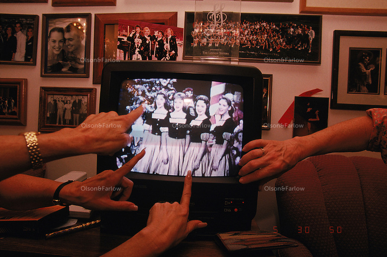 The Lennon sisters in their dressing room watch an old tape of them performing on the Lawrence Welk Show.  Branson Missouri is a town of country music theaters that is the number ONE bus destination in the country and the number TWO tourist destination (second only to Orlando).  There are more theater seats in Branson than on Broadway and they have over 1.5 billion tourist dollars flow into their little town annually even though there are no interstate highways in the area.<br /> Once an ancient sea, its uplifted floor untouched by scouring glaciers that stopped to the north.  Eons of erosion carved deep valleys into the Ozarks crusty limestone plateau, transforming its flat surface into the unlikely role of hills.  They march nearly level into the distance, and peak at 2,600 feet in Arkansas's Boston Mountains...  Ozarks region in Missouri and Arkansas by Randy Olson for National Geographic Magazine.