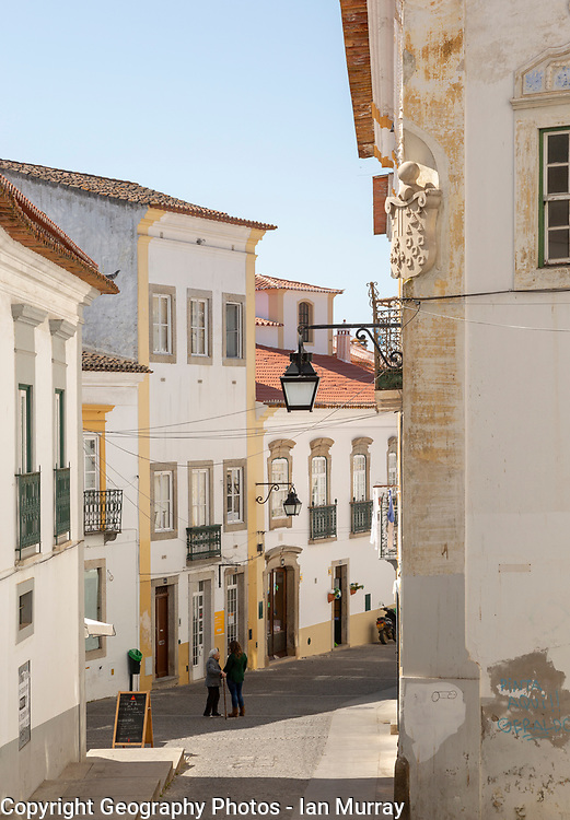 People talking in the street in neighbourhood in the city centre of Evora, Alto Alentejo, Portugal, southern Europe