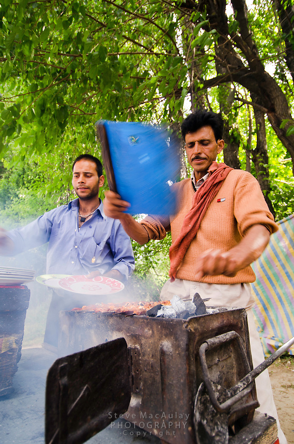 Kashmiri men grilling kabobs on small charcoal grill alongside road, Srinagar, Kashmir, India.
