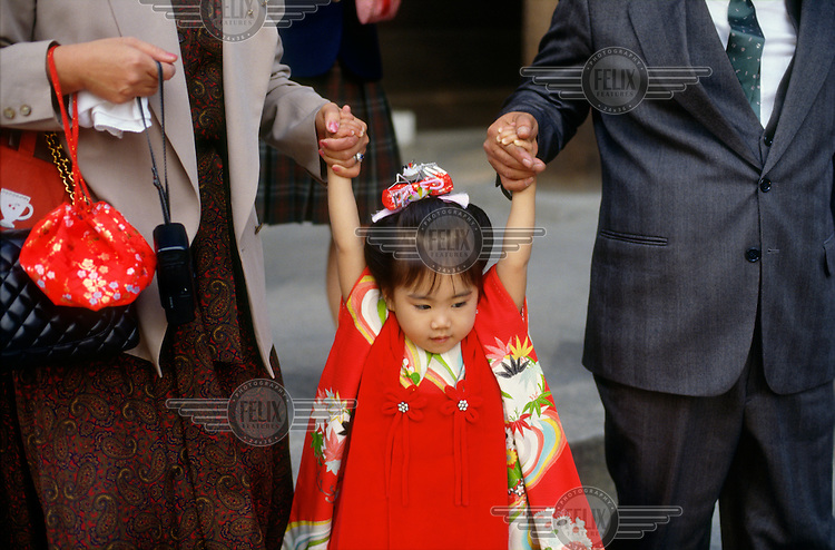 A young girl in traditional dress holds her parents hands at the annual Shichigosan (meaning 'Seven Five Three') festival. During the festival, girls, aged three and seven, and boys, aged three and five, are brought to the Shinto shrines for prayers to ensure good health and growth...