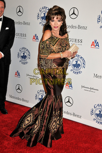 JOAN COLLINS .The 30th Annual Carousel Of Hope Ball at the Beverly Hilton Hotel, Beverly Hills, California, USA..October 25th, 2008.full length brown gold sheer beads beaded pattern clutch bag dress silk satin fishtail .CAP/ADM/BP.©Byron Purvis/AdMedia/Capital Pictures.
