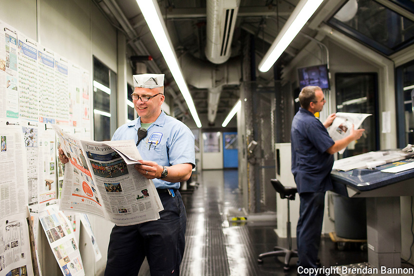Scott Newman wearing a  traditional pressman's hat in the quiet room where pressmen run regular color and quality checks as the paper goes through its daily press run. The pressmen can make real-time changes to color as the paper is being printed.  The newspaper has been owned by billionaire investor Warren Buffett since 1977, Buffett announced the purchase of an additional 63 newspapers in May of 2012. Photo: Brendan Bannon, Buffalo, NY, June 8, 2012.