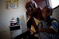 Mother and son, somali refugees, receive treatment in the Kharaz refugee camp clinic In  Yemen on Tuesday November the 27th 2007. THe camp, former military barracks, hosts 9000 somali refugees, most of which have become stable residents, completely dependent on humanitarian donations.  Somalis are allowed to work in Yemen, but due to the a 35% unemployment rate in the country, most of them remain jobless.///..Ever since the collapse of the Siad Barre regime in 1991 Somali men, women and children have been arriving at the port of Bosasso to buy passage in small open fishing boats to Yemen, where they are given automatic political asylum..The  boat trip, costing from 70 to 150 usd per person, can be often fatal due to the roughness of the sea, the overcrowded boats and the merciless of the smugglers..On the night of Nov 29 2007 a small fishing boat while trying to download it's load of refugees a few hundred meters from the Yemeni  shores of Meifa Haja, flipped over and was overwhelmed by the constant waves. of its 130 passengers, only 42 reached the UNHCR ( United Nations High Commissioner for Refugees )  refugee center in Meifa. 30 bodies where recovered the next day.  the rest are still unaccounted for.. UNHCR  estimates more than 80.000 somali refugees live  in the country residing mostly in shanty towns in Sana'a' and Aden.