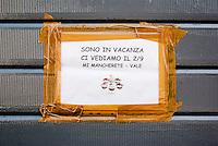 """Milano, cartello di """"chiuso per ferie"""" sulla saracinesca chiusa di una attività commerciale --- Milan, """"closed for vacation"""" sign (""""i'm on holiday, i will miss you"""") on the closed shutter of a commercial activity"""