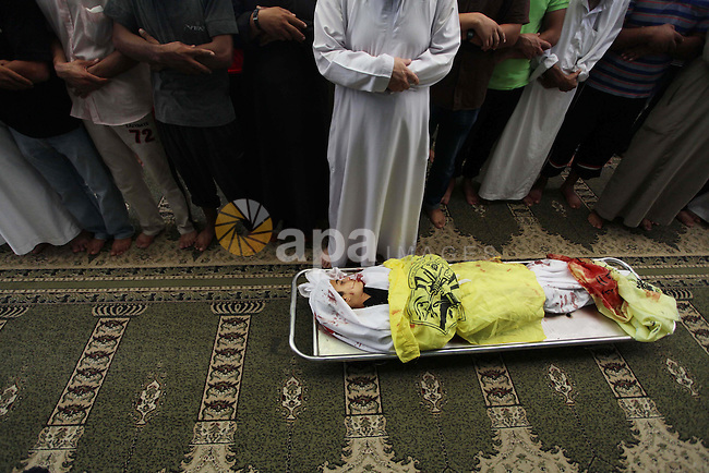 Palestinians pray over the body of Ahmed Al-Masri, 14, who witnesses said was killed in an Israeli airstrike, during his funeral at a mosque in Deir Al-Balah town in Central Gaza Strip, August 10, 2014. Palestinian negotiators will remain in Cairo for an urgent meeting with the Arab League on Monday to discuss the Gaza crisis, Egypt's state MENA news agency said. The Palestinian delegation had said it was likely to abandon Egyptian-mediated talks on Sunday unless Israel agreed to return to the table without pre-conditions. Photo by Ashraf Amra