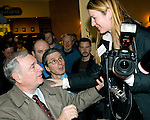 Canadian Prime Minister Paul Martin (left) tries to help Deddeda, on assignment for the Victoria Times Colonist newspaper, down off of a chair at a coffee shop in Courtenay, British Columbia, Canada on Thursday February 26, 2004.