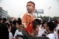 Spectators watch the Olympic torch pass by during the Nanjing, China, leg of the 2008 Olympic Torch Relay.  .