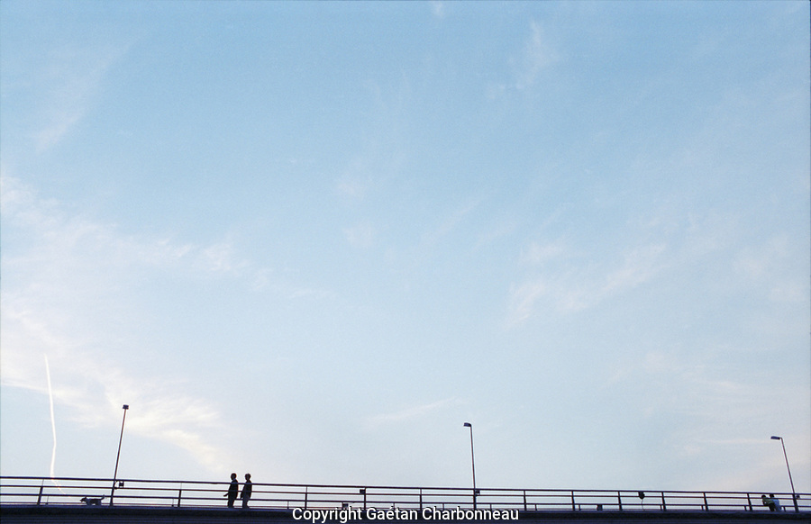 A couple walking a dog, under a blue sky, seen from a distance.