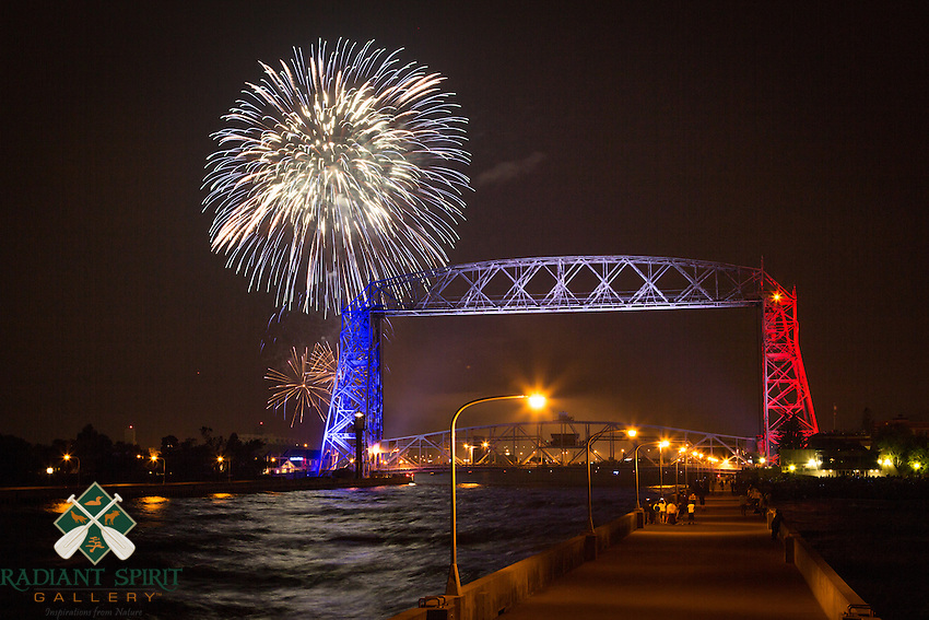 &quot;Duluth Fireworks&quot;<br /> Duluth puts on a grand fireworks show on Independence Day. Like many revelers, the Aerial Lift Bridge is decked out in red, white, and blue for the occasion. The mood is festive, the lake breeze is invigorating, and the waves crashing into shore complete the experience.<br /> <br /> The Aerial Lift Bridge is one of the most-recognized iconic landmarks of Duluth. In a mere 55 seconds, the bridge rises to 138 feet, making it the quickest and biggest lift bridge in the world.