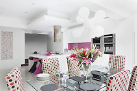 The dining chairs around the glass-topped table are upholstered in a polka-dot fabric which echoes the pink signature in the kitchen