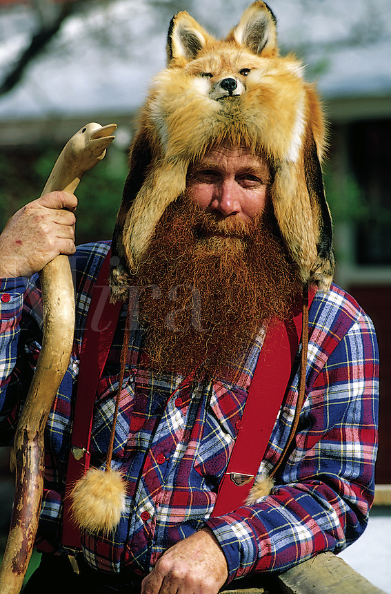 A man portrays an Alaskan 'Sourdough' (early settler prospector  mountain man,) posing in a fox hat, holding a carved walking stick. Alaska.