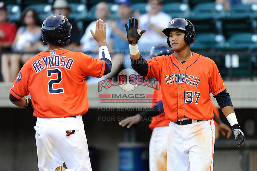 Third baseman Luis Reynoso (2) of the Greeneville Astros is congratulated after scoring a run by Cesar Carrasco in a game against the Bristol Pirates on Friday, July 25, 2014, at Pioneer Park in Greeneville, Tennessee. Greeneville won, 9-4. (Tom Priddy/Four Seam Images)