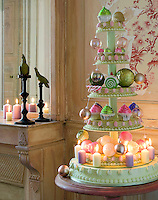 A series of cakes on a multi-tiered stand have been decorated with Christmas baubles and candles to create a fun and colourful alternative Christmas tree