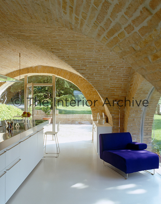 Sunlight bounces off the white floors illuminating the vaulted brick ceiling of the kitchen