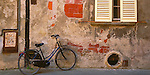 Lucca, Tuscany, Italy<br /> A bicycle leans against a weathered brick and plaster wall with shuttered window in the town of Lucca