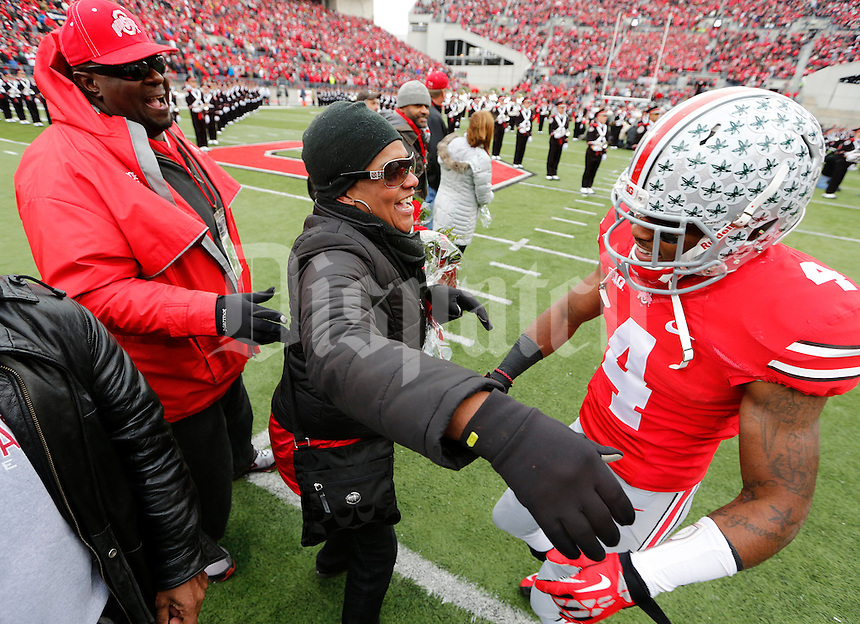 Ohio State Buckeyes safety C.J. Barnett (4) greets family during Senior Day celebration before the college football game between the Ohio State Buckeyes and the Indiana Hoosiers at Ohio Stadium in Columbus, Saturday afternoon, November 23, 2013. The Ohio State Buckeyes defeated the Indiana Hoosiers 42 - 14. (The Columbus Dispatch / Eamon Queeney)