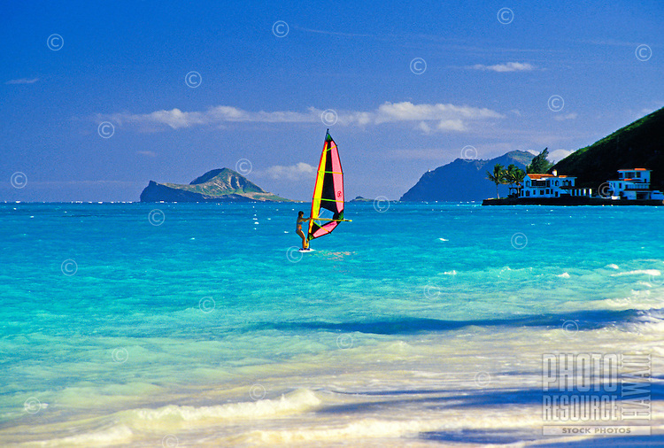 Lone windsurfer in calm blue-green waters off Lanikai beach with Rabbit island in the distance.