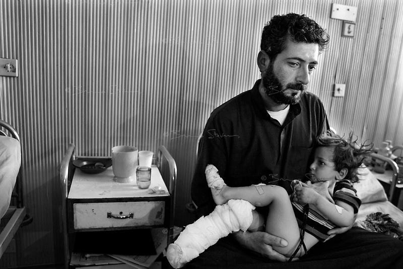 Hilla, Iraq, April 2, 2003.Hilla Hospital, Majid Khalil, with his son Hassan, 2 1/2 (who lost his right foot). Majid mourns his wife Haula, 25, his son Ahmed, 8, his daughter Sara, 4,  and his mother in law, all killed in the family home by a US cluster bombs.