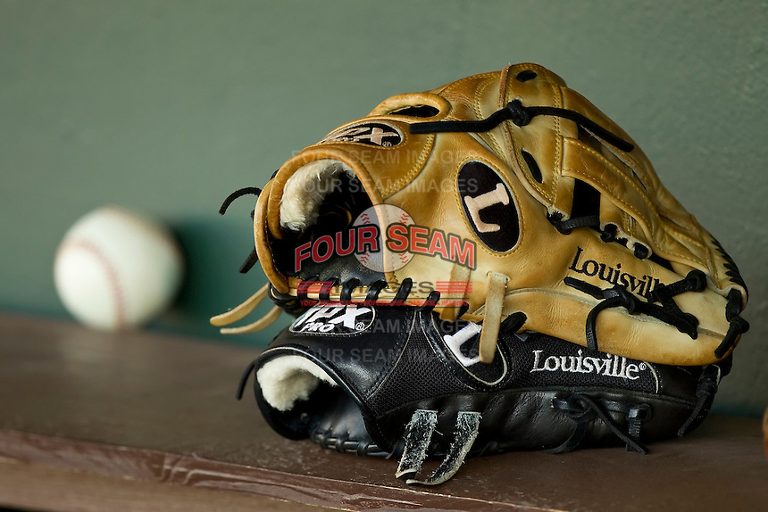 Two Louisville Slugger baseball gloves sit in the Charlotte Knights dugout prior to the game against the Durham Bulls at Knights Stadium on August 2, 2011 in Fort Mill, South Carolina.  The Bulls defeated the Knights 18-3.   (Brian Westerholt / Four Seam Images)