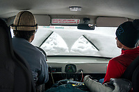 The view through the snow covered front window of a car while driving through Kyrgyzstan.