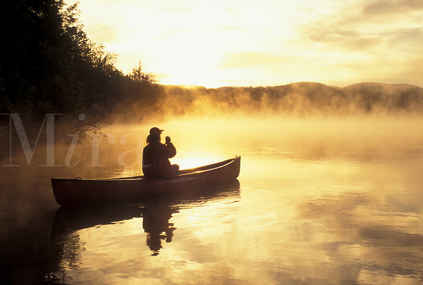 canoeing, canoe, sunset, sunrise, Vermont, VT, Woman paddling a canoe on Mollys Falls Pond at sunrise in the mist.