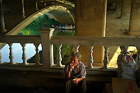 A man smokes a cigarette under a bridge over the Perfume river in Hue, Vietnam on 26 February 2010.
