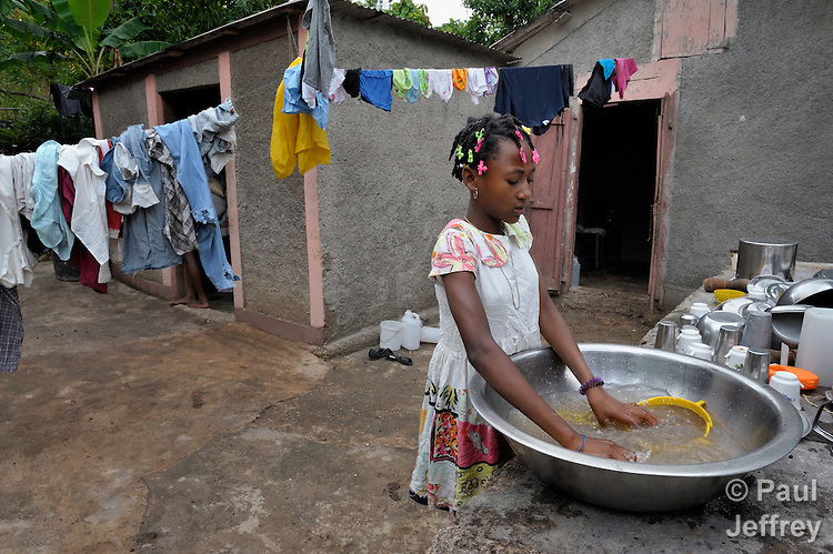 "Romage Jean Louis, 11, seen here washing dishes at her home, is a Peace Pal in the southern Haitian village of Mizak. Peace Pals is a program of the World Peace Prayer Society, which promotes the message ""May Peace Prevail on Earth"" as a simple, universal expression to unite the hearts of all people in a common desire and hope for peace on Earth. Peace Pals provides a safe and nurturing environment for children to gather to play and learn lessons that organizers hope will lead to generational changes in attitudes about self-worth, care for the environment, personal health & hygiene, conflict resolution, respect for all persons and encouragement to be ""peacebuilders"" at all levels. In Mizak, Peace Pals is sponsored by Haitian Artisans for Peace International (HAPI)."