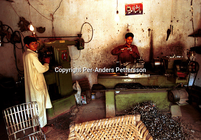 Falak Naz, age 26, far right is making barrels for guns, shotguns and Kalashnikovs in an underground weapons factory on September 22, 2001 in Darra, a village about 40 kilometers south of Peshawar, Pakistan. These factories have made copies of weapons for over one hundred years and they are used in conflicts in Afghanistan, The Balkans and Kashmir and other areas. These weapons are also smuggled into Afghanistan to the Taleban movement..Photo: Per-Anders Pettersson/ iAfrika Photos......