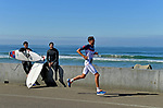 OCEANSIDE, CA - APRIL 7:  Jan Frodeno of Germany runs past surfers on the strand during the IRONMAN 70.3 Oceanside Triathlon on April 7, 2018 in Oceanside, California. (Photo by Donald Miralle for IRONMAN)