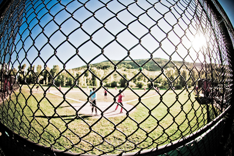 Unusual fisheye view through a chain link fence of young baseball players.