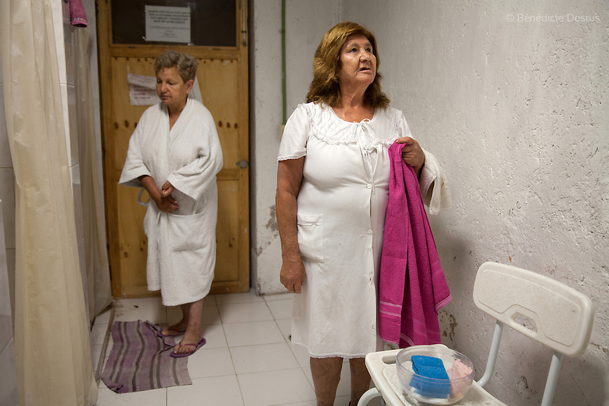 Sonia (L) and Gloria (R), both residents of Casa Xochiquetzal, take a shower at the shelter in Mexico City, Mexico on September 3, 2013. Casa Xochiquetzal is a shelter for elderly sex workers in Mexico City. It gives the women refuge, food, health services, a space to learn about their human rights and courses to help them rediscover their self-confidence and deal with traumatic aspects of their lives. Casa Xochiquetzal provides a space to age with dignity for a group of vulnerable women who are often invisible to society at large. It is the only such shelter existing in Latin America. Photo by Bénédicte Desrus