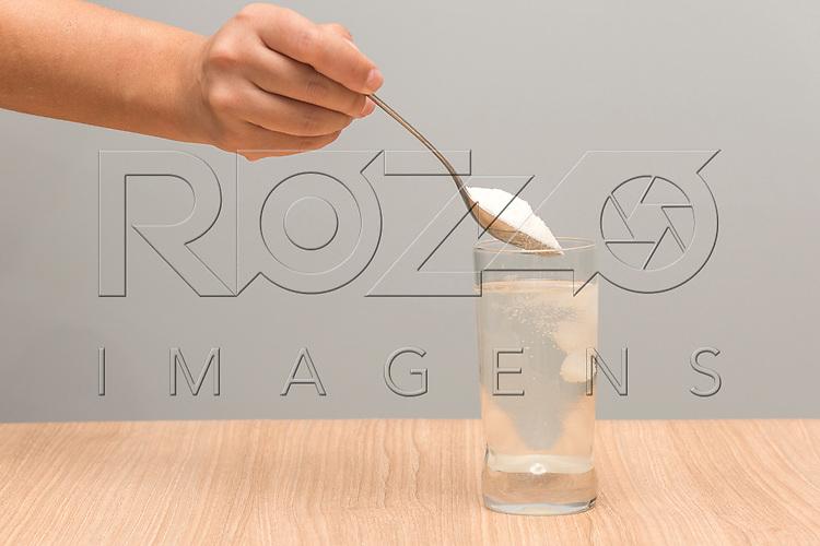 Pessoa colocando uma colher de açúcar em um copo com água, 2017.