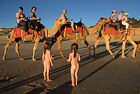 Two little girls watch tourists riding camels along the beach in Australia.