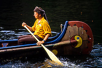 caucasian man with Indian hat paddling an Indian canoe in Disney World, Florida, USA