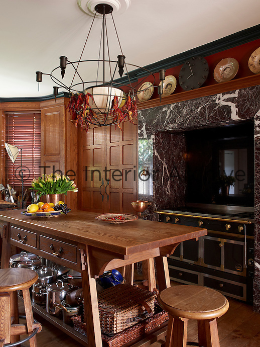 Rich oak panelling in the kitchen frames a marble alcove which houses an industrial range