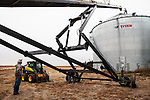 Brett Oelke, left, watches as workers prepare to store the corn harvest on his family's 6,000-acre farm outside of Hoxie, Kan., on Friday, Oct. 12, 2012. As historically dry conditions continue, farmers from South Dakota to the Texas panhandle rely on the Ogallala Aquifer, the largest underground aquifer in the United States, to irrigate crops. After decades of use, the falling water level ? accelerated by historic drought conditions over the last two years ? is putting pressure on farmers to ease usage or risk becoming the last generation to grow crops on the land. Farmers like Mitchell Baalman (not pictured) and Brett Oelke are part of a farming community in in Sheridan County, Kansas, an agricultural hub in western Kansas, who have agreed to cut back on water use for crop irrigation so that their children and future generations can continue to farm and sustain themselves on the High Plains.