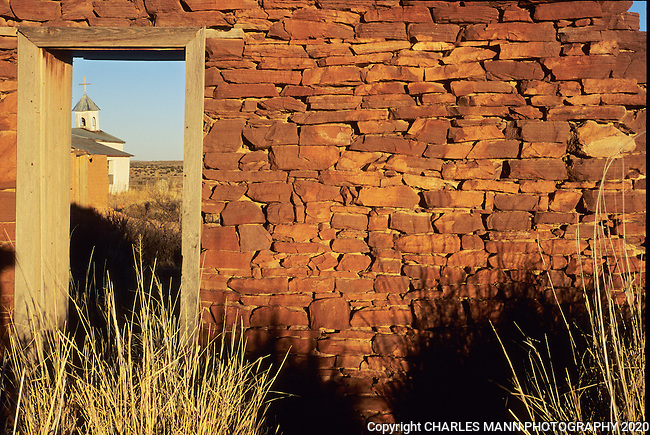 The late afternoon sun casts the shadows of tall prairie grasses onto the collapsing stone walls of a settlement in the abandoned village of Guadalupe a few miles from Fort Sumner, New Mexico.