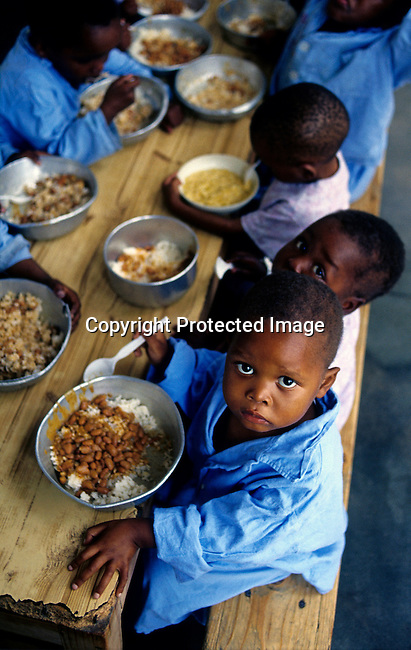.Aids orphans eat lunch on July 6, 2001 at Murchison hospital, outside Port Shepstone in Southern Natal, South Africa. It's estimated that it will be one million orphans related to the Aids epidemic in South Africa by 2004. About 5,6 million South Africans are infected with the virus and about 1000 day every day. .