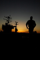 Crossing the flight deck at dusk aboard USS Abraham Lincoln.