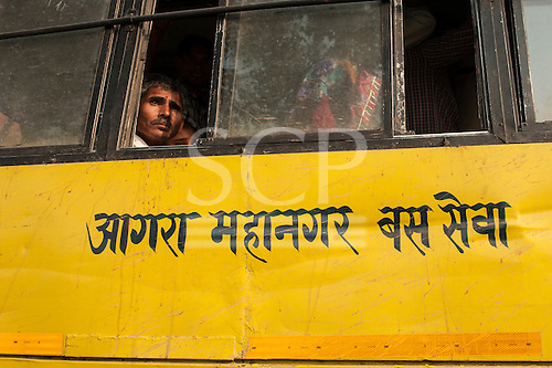 Agra, Utar Pradesh, India. People looking out of a yellow Agra bus with 'Agra Metropolitan Bus Service' written in Hindi.